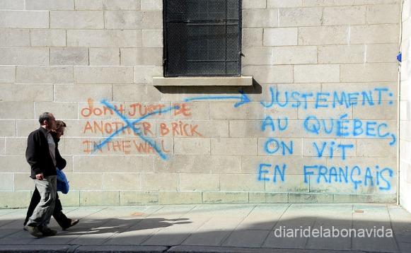 """En resposta a una pintada en anglès (""""no siguis un totxo més a la paret""""), podem llegir """"precisament al Quebec vivim en francès"""""""
