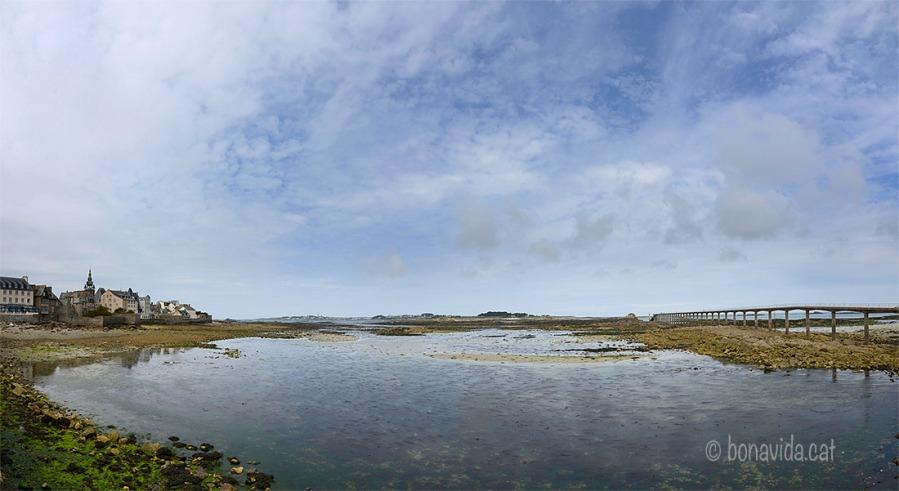 Roscoff a l'esquerra, davant l'illa de Batz, i a la dreta el llarg pont per arribar al ferri si la marea és baixa