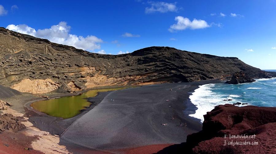 El verd intens de la Laguna los Clicos destaca sobre la sorra negra de la platja