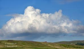 Un núvol corona una típica granja islandesa